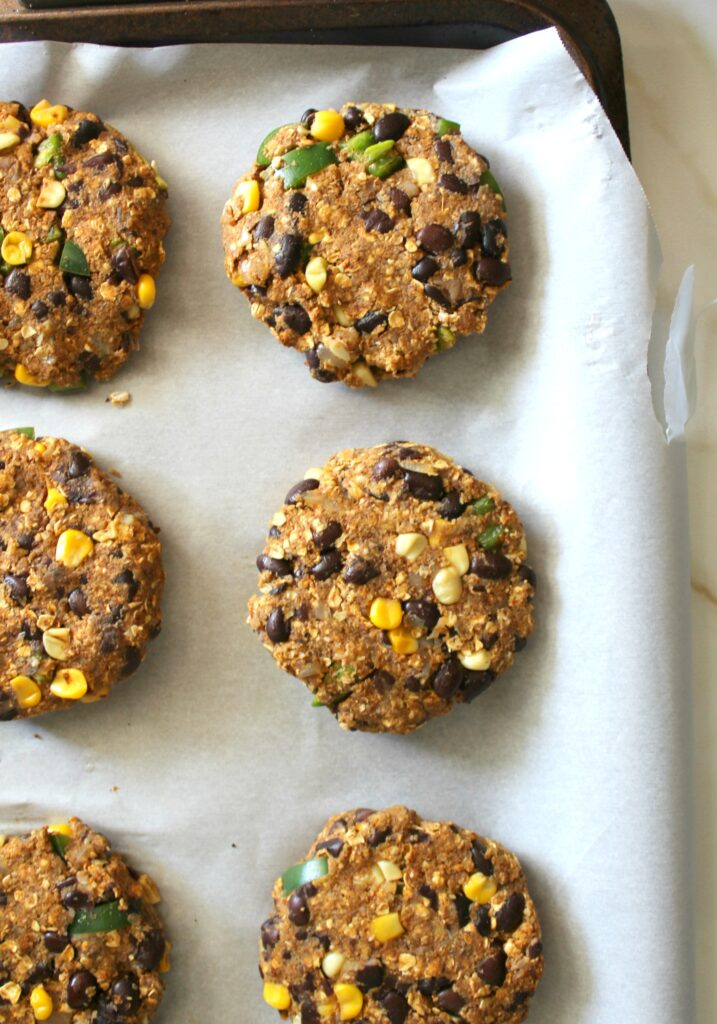 These Spicy Black Bean Burgers are simple, tasty and vegan! Make them ahead of time and keep them in the freezer for an easy weeknight dinner!   ThisSavoryVegan.com