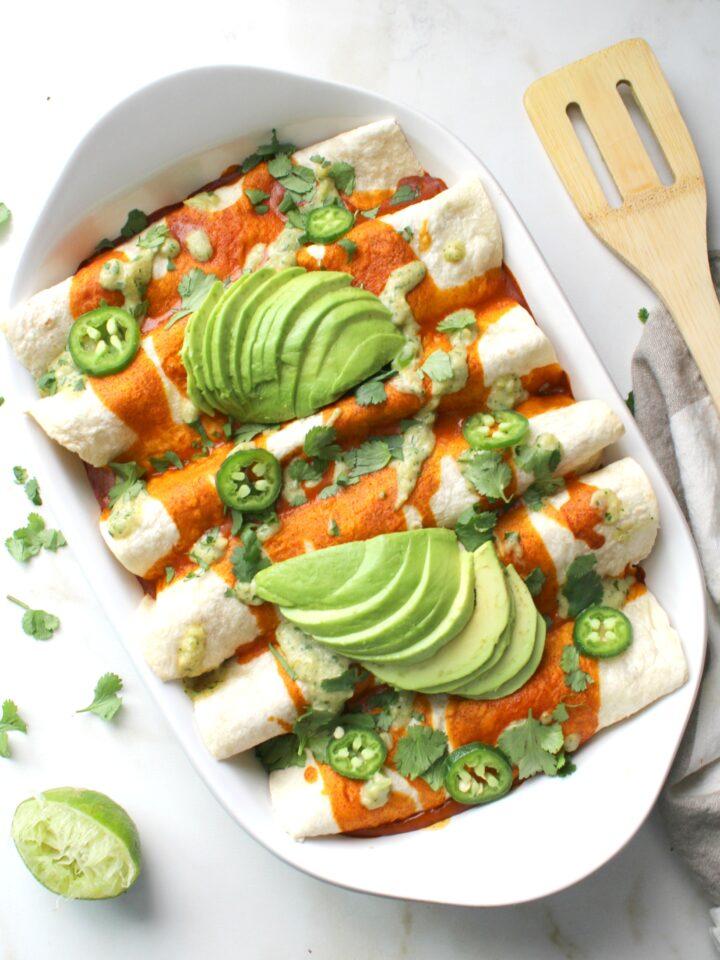 TheseBlack Bean Tofu Scramble Vegan Enchiladas are loaded with a hearty tofu scramble of black beans & veggies and are topped off with a green chili cream sauce   ThisSavoryVegan.com #vegan #veganenchiladas