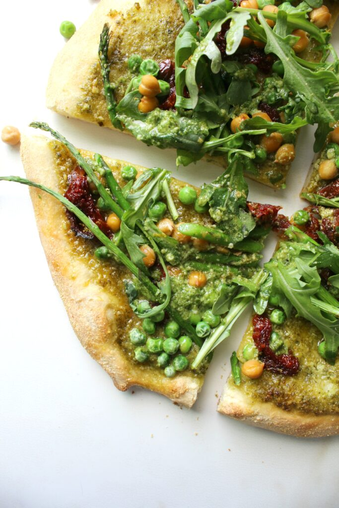 A fresh mix of flavors and veggies comes together with thisSpring Greens Pesto Pizza. A crunchy crust, fresh pesto, sun-dried tomatoes, chickpeas, asparagus, peas and arugula make a light vegan pizza!   ThisSavoryVegan.com #vegan #veganpizza