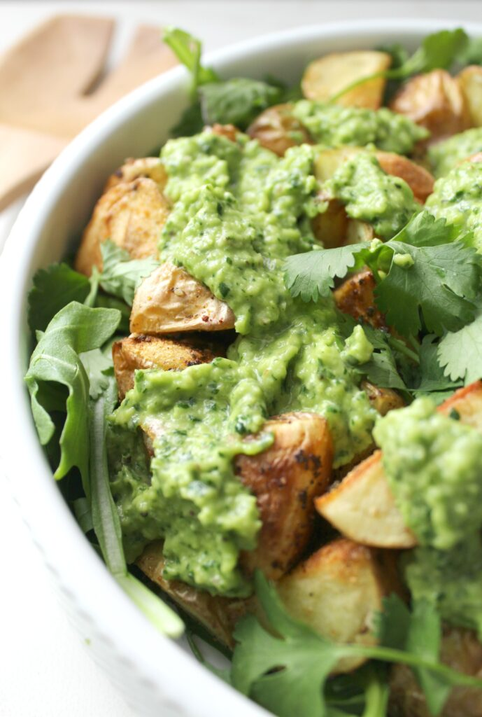 ThisVegan Spring Potato Salad with Creamy Dreamy Green Sauce is traditional potato salad's lighter, greener and tastier cousin. Warm garlicky potatoes are tossed with fresh arugula and a green sauce that is packed with flavor   ThisSavoryVegan.com #vegan #spring #potatosalad