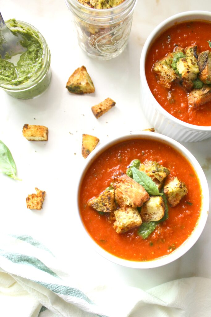 Say so-long to store bought soup with thisTomato Basil Soup with Pesto Ciabatta Croutons. Made simple by using canned tomatoes and made extra delicious with roasted garlic. A quick vegan recipe loaded with fresh flavors   ThisSavoryVegan.com #vegan #soup