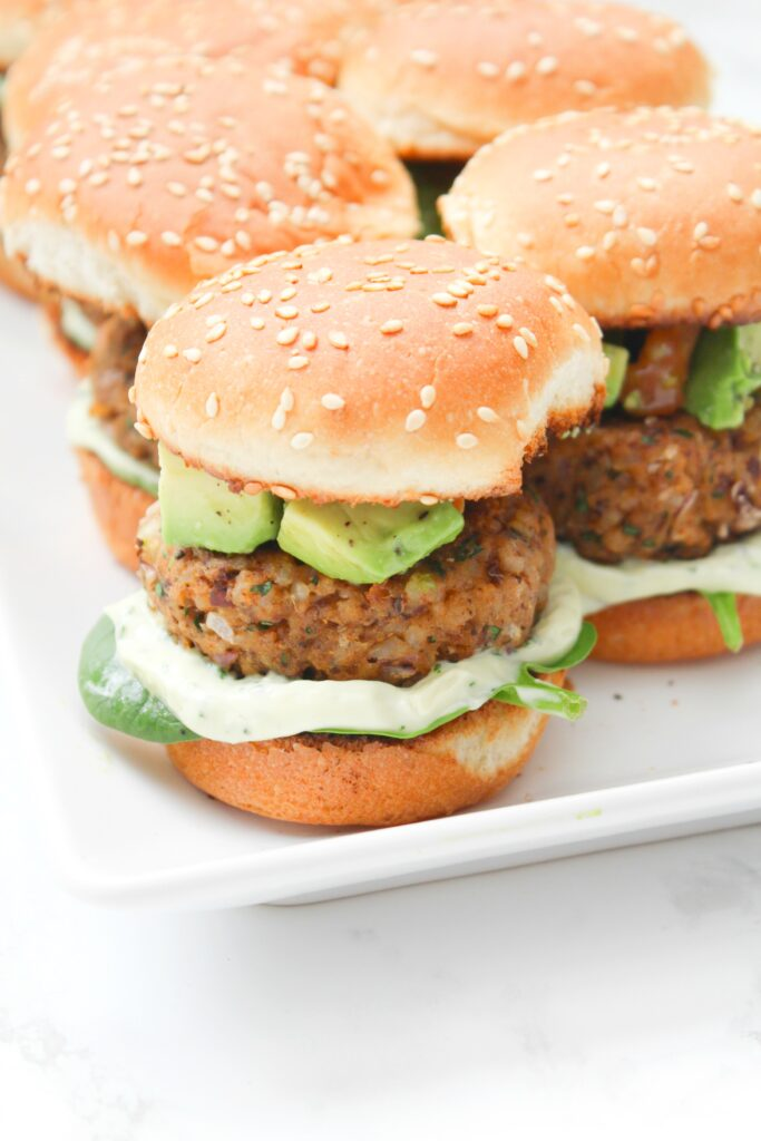 These Zesty Brown Rice Black Bean Vegan Sliders with Basil Aioli are the perfect party appetizer. Topped off with an avocado & tomato salsa | ThisSavoryVegan.com #thissavoryvegan #vegan #sliders