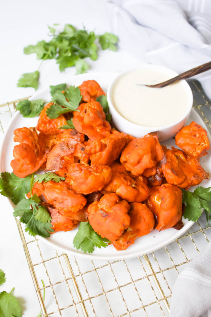 Flavored from the inside out and perfectly crispy, this really is The Best Baked Buffalo Cauliflower out there. Served with vegan ranch! | ThisSavoryVegan.com #thissavoryvegan #buffalocauliflower #vegan