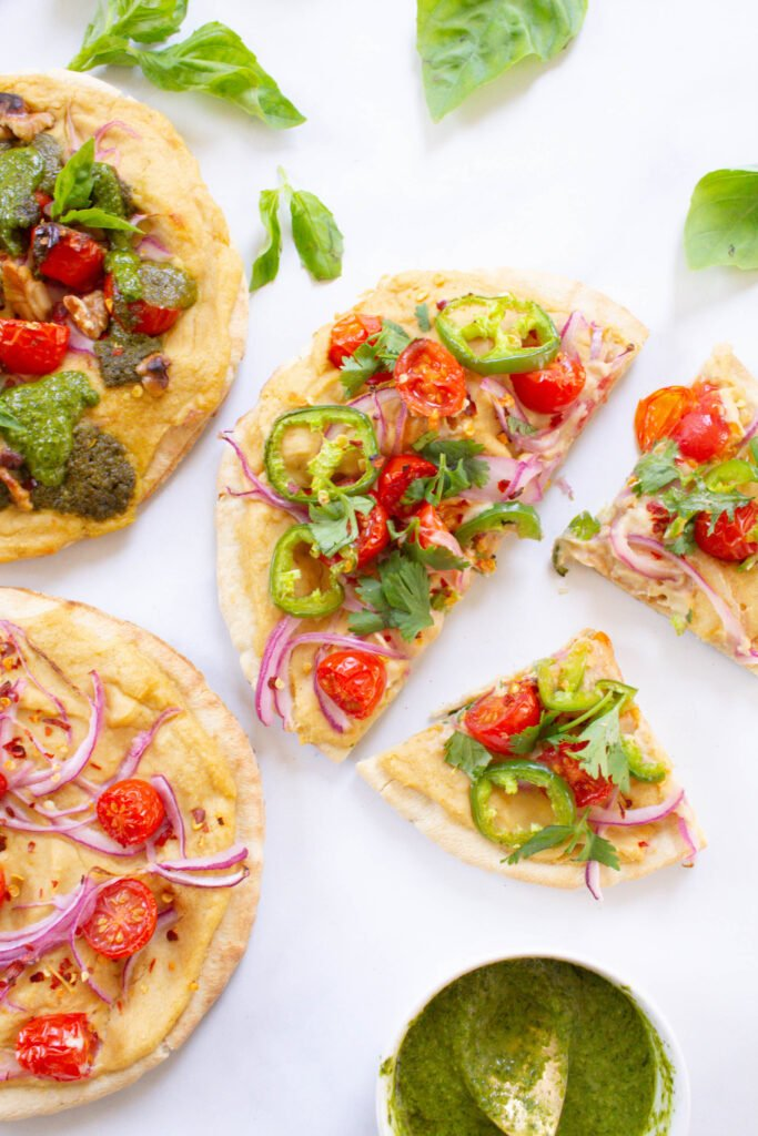 Hummus Pita Pizzas 3 Ways - making vegan pizza at home is super easy when you use hummus and pita bread as your base. Add your favorite toppings and bake   ThisSavoryVegan.com #thissavoryvegan #vegan #veganpizza
