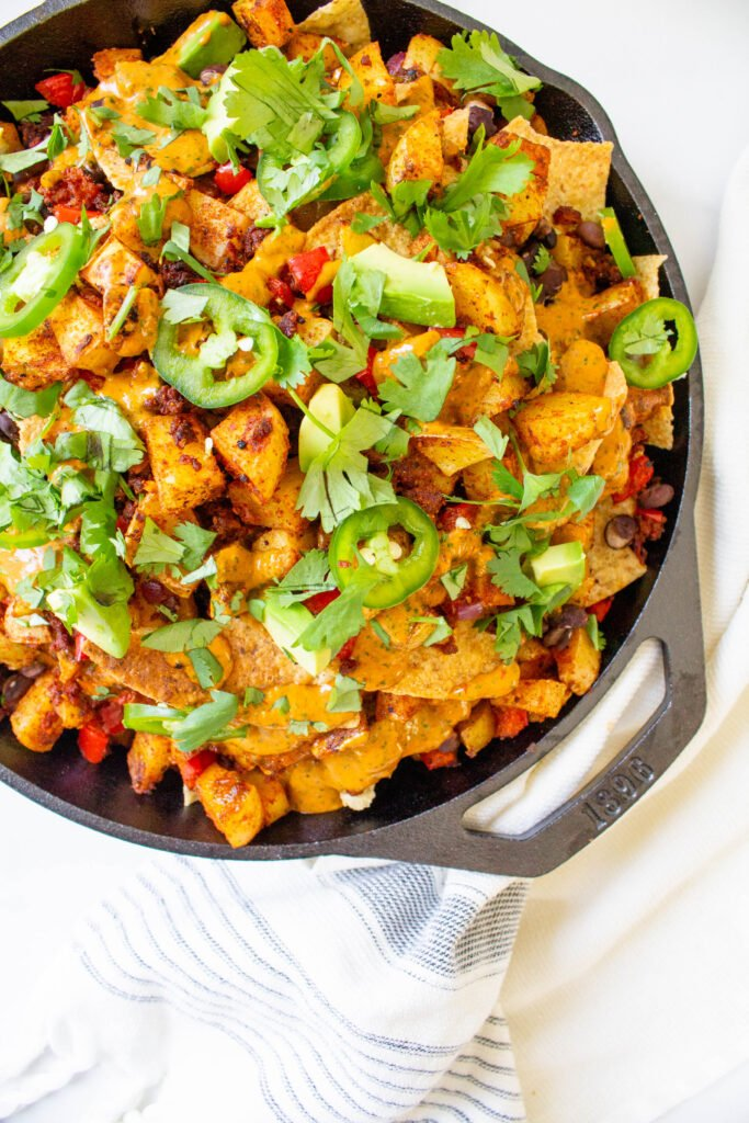 Get ready for your next party with these Potato Soyrizo Skillet Nachos with Chipotle Cilantro Sauce. Loaded with black beans, veggies and vegan sausage   ThisSavoryVegan.com #thissavoryvegan #vegannachos #vegangamedaysnacks