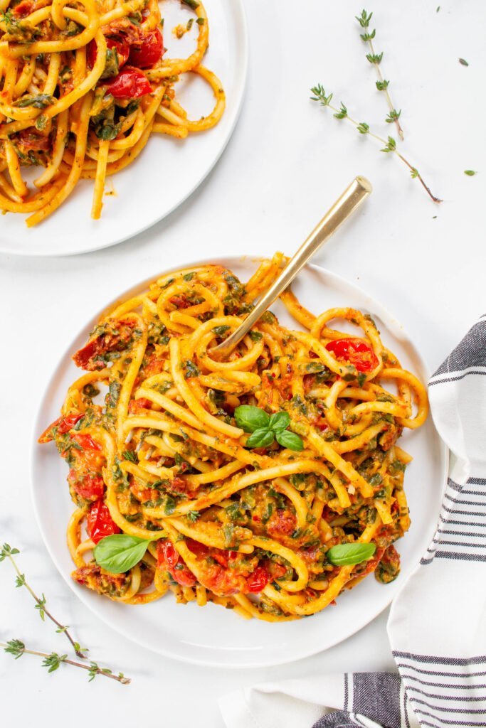 This Creamy Vegan Pumpkin Bucatini is filled with cherry tomatoes, spinach and garlic. It is lightened up by using pumpkin puree and hummus for the creamy sauce   ThisSavoryVegan.com #thissavoryvegan #veganpasta #pumpkinpasta