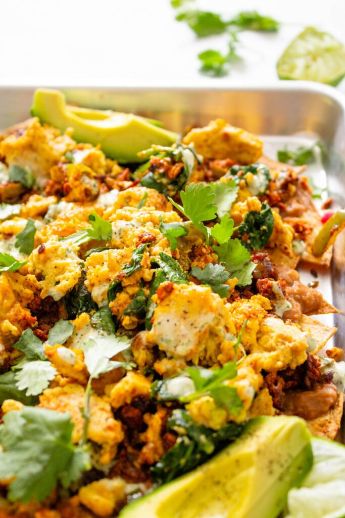 These Vegan Breakfast Nachos are loaded with air fryer chips, vegan eggs, refried beans, soyrizo, veggies and vegan cilantro ranch. Perfect for brunch at home | ThisSavoryVegan.com #thissavoryvegan #veganbrunch #vegannachos