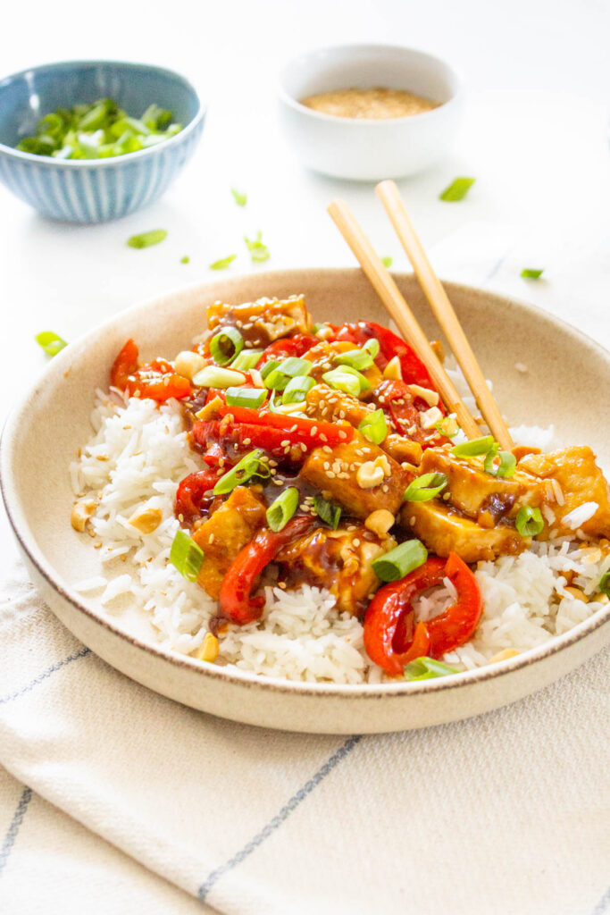 These Vegan Kung Pao Tofu Bowls are a better than takeout vegan dinner at home. Filled with sticky, savory & sweet tofu, red bell pepper & rice   ThisSavoryVegan.com #thissavoryvegan #kungpao #tofurecipes