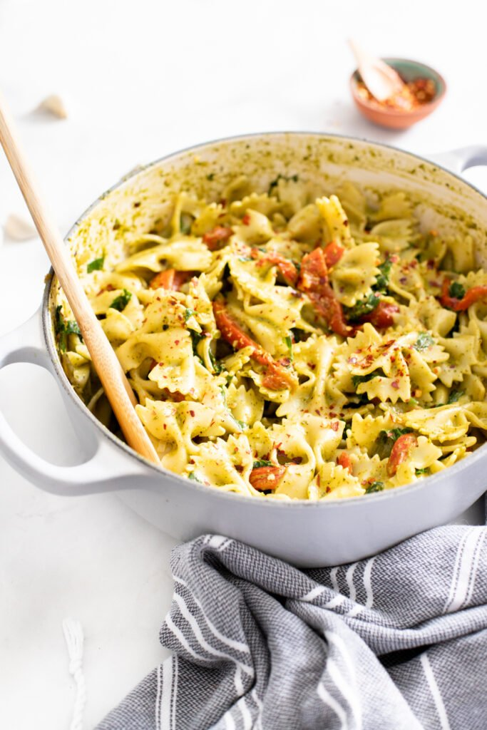 This Creamy Vegan Pesto Pasta is loaded with roasted red peppers, kale, fresh basil and lemon zest. A one-pot vegan dinner that is ready in 30 minutes   ThisSavoryVegan.com #thissavoryvegan #veganpasta #pestopasta