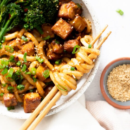 These Spicy Peanut Udon Noodle Bowls are loaded with crispy baked tofu, broccolini and saucy noods. A savory and healthy vegan dinner | ThisSavoryVegan.com #thissavoryvegan #tofunoodlebowls #vegandinnerideas