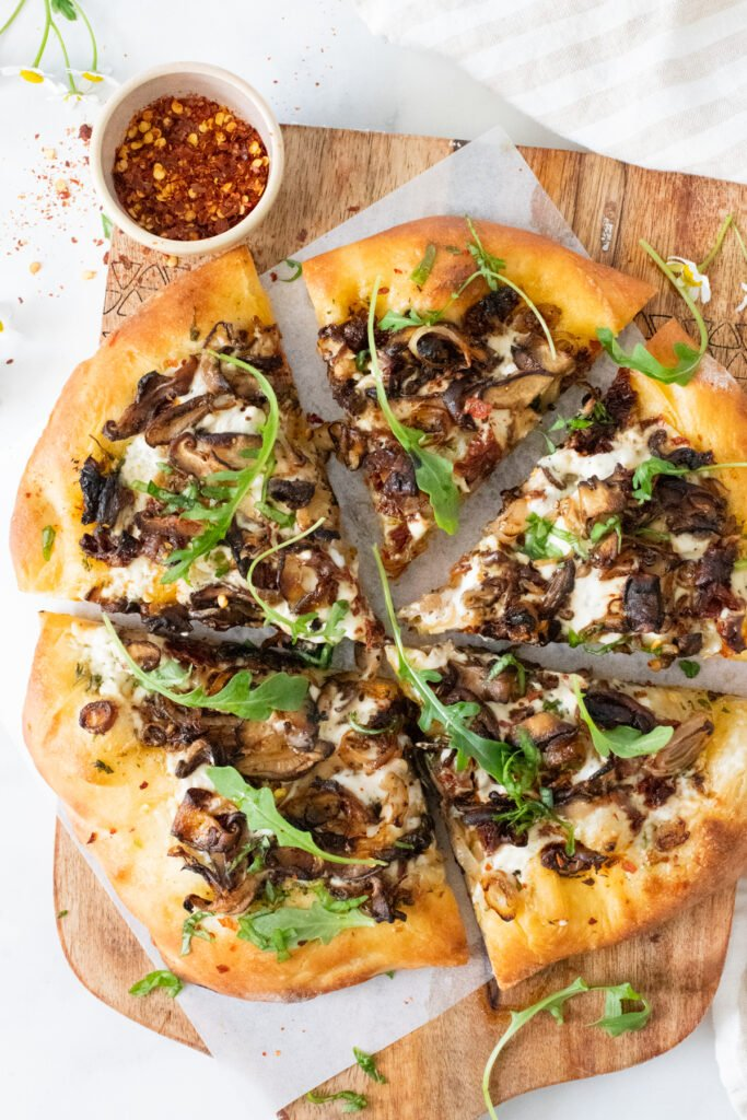 This Vegan Mushroom & Shallot White Pizza is better than takeout! Plenty of herbs, sun-dried tomatoes, creamy sauce & caramelized mushrooms | ThisSavoryVegan.com #thissavoryvegan #veganpizza #veganwhitepizza