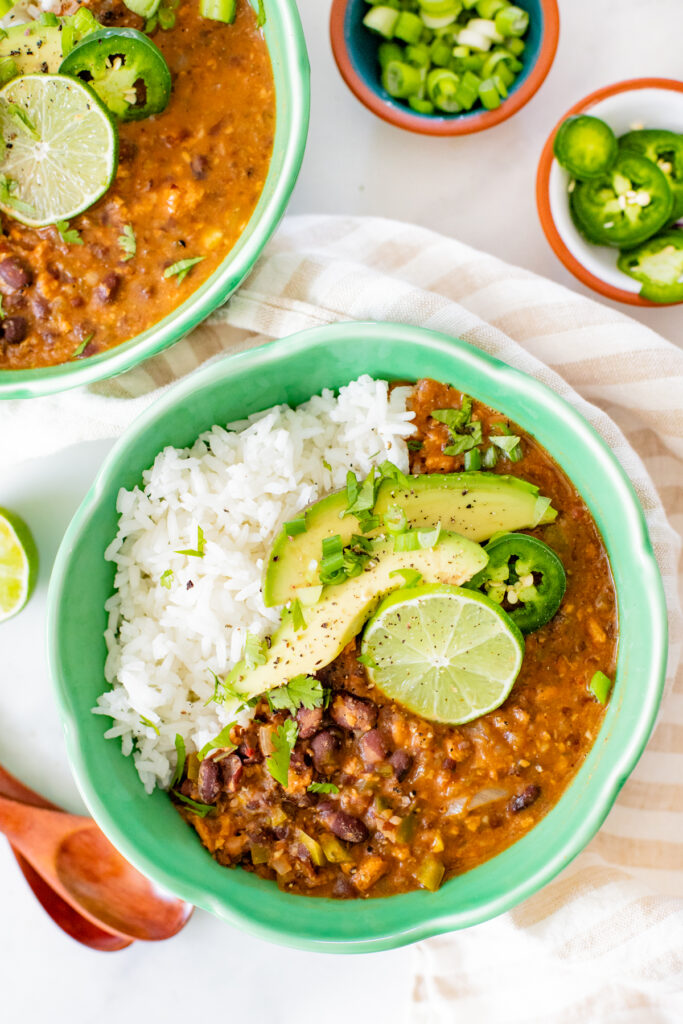 Perfect for a cold weeknight, this Slow Cooker Black Bean Soup is healthy, comforting and packed full of fiber and protein. Spice it up with your fave toppings   ThisSavoryVegan.com #thissavoryvegan #slowcookerrecipes #slowcookersoup