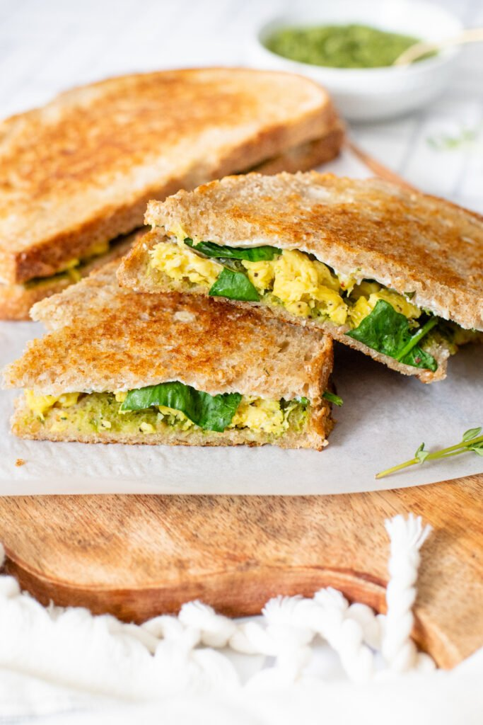Make brunch at home with these Vegan Pesto & Egg Breakfast Sandwiches. The perfect combo of vegan eggs, cream cheese, spinach & pesto | ThisSavoryVegan.com #thissavoryvegan #veganbrunchideas #veganbreakfastideas