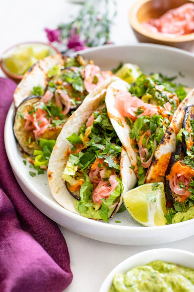 These Roasted Eggplant Vegan Tacos are layered with a creamy herb sauce, pickled onions, romaine and a drizzle of hot sauce | ThisSavoryVegan.com #thissavoryvegan #vegantacos #eggplantrecipes