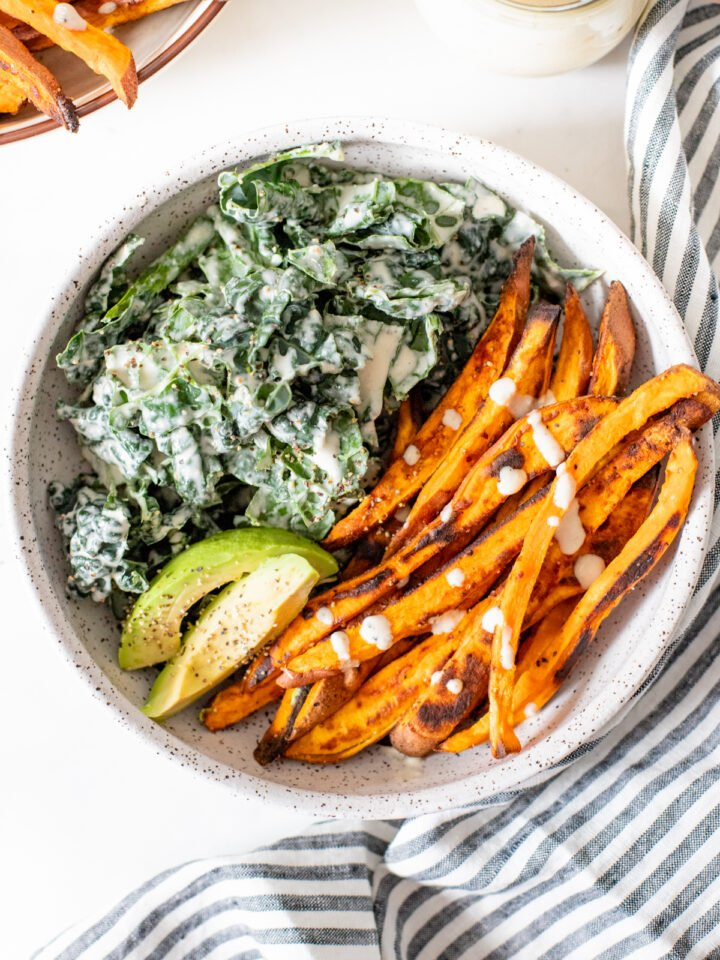 This Tahini Kale Caesar with Sweet Potato Fries is the perfect weeknight dinner. Crispy baked fries, vegan kale caesar and slices of avocado | ThisSavoryVegan.com #thissavoryvegan #kalecaesar #vegandinnerideas