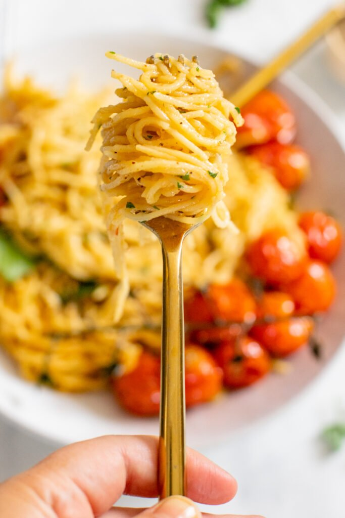 This Creamy Vegan Garlic Pasta has a simple sauce and is topped with burst tomatoes on the vine. A quick & delicious vegan dinner idea   ThisSavoryVegan.com #thissavoryvegan #veganpasta #summerpasta