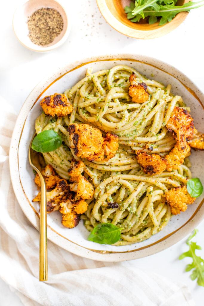This Vegan Pesto Bucatini with Crispy Cauliflower is a quick and easy vegan dinner! Homemade argula-basil pesto & seasoned baked cauliflower over a bed of pasta | ThisSavoryVegan.com #thissavoryvegan #veganpesto #veganpasta