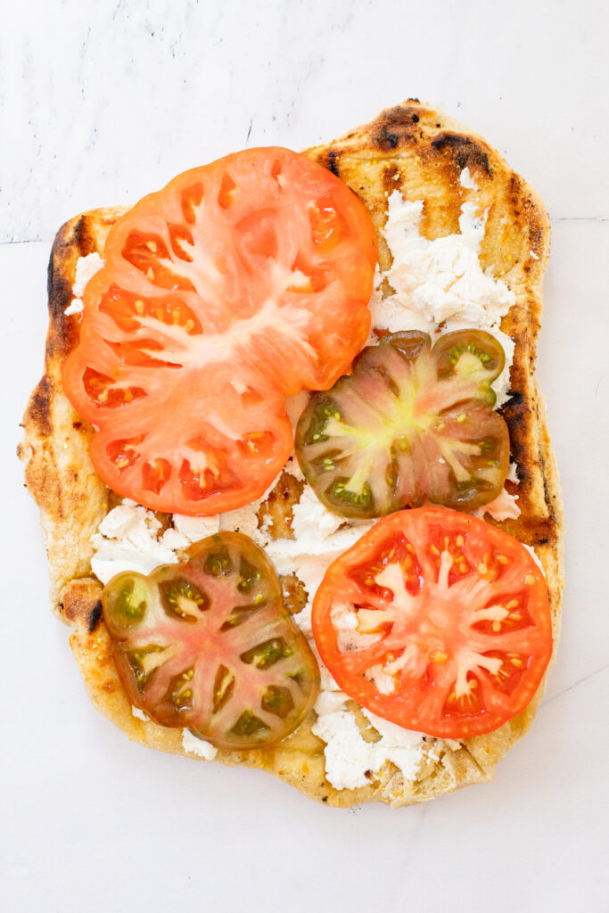 This Grilled Heirloom Tomato Pizza is layered with vegan ricotta, thick slices of heirloom tomatoes, balsamic glaze & fresh basil | ThisSavoryVegan.com #thissavoryvegan #veganpizza #grilledpizza