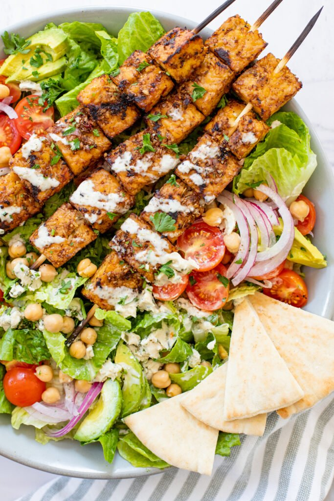 This Grilled Tempeh Greek Salad with Creamy Vegan Greek Dressing is a must make! The perfect vegan salad - restaurant quality at home   ThisSavoryVegan.com #thissavoryvegan #greeksalad #tempehskewers