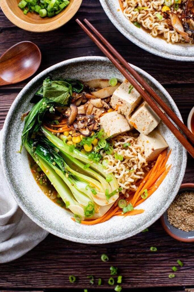 This Simple Vegan Ramen is comfort in a bowl. Crispy mushrooms & shallots, tofu, bok choy and a tasty vegan broth! A must make! | ThisSavoryVegan.com #thissavoryvegan #veganramen #fallrecipes