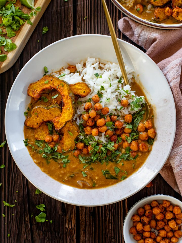 This Acorn Squash Curry with Lentils & Roasted Chickpeas is comfort in a bowl. The roasted squash is divine and the curry is perfectly spicy | ThisSavoryVegan.com #thissavoryvegan #vegancurry #squashrecipes