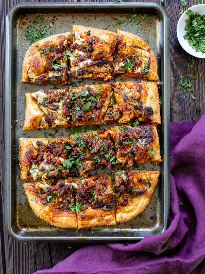 This Vegan BBQ Bacon Pizza is better than any take-out I've had and a great dinner to make on a Friday at home. Layered with caramelized onions, tempeh bacon and a creamy sauce | ThisSavoryVegan.com #thissavoryvegan #veganpizza #plantbasedpizza