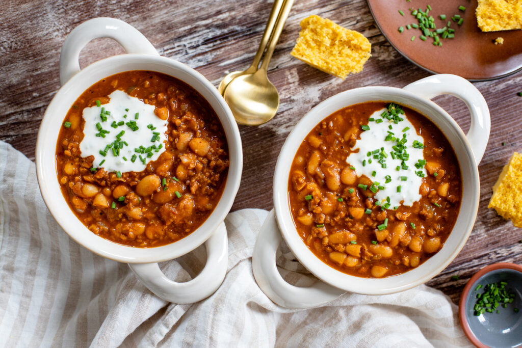 This Vegan Pumpkin Chili is hearty, healthy and tasty. Filled with white beans, vegan beef crumbles, veggies and plenty of seasonings. The Fall recipe you need to try   ThisSavoryVegan.com #veganchili #fallrecipes #veganstew